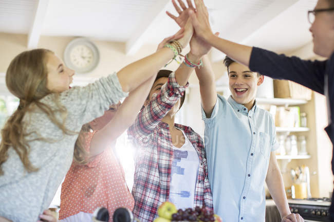 Группа подростков делать высокие пять в гостиной — стоковое фото