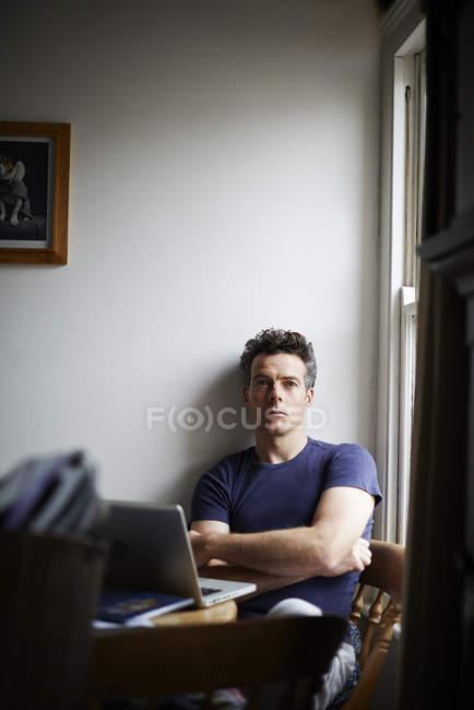Человек, сидя за столом с открытым ноутбук глядя — стоковое фото