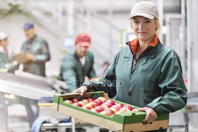 Портрет впевнено жіночий працівник перевозять коробку яблук в харчової переробки рослин — стокове фото