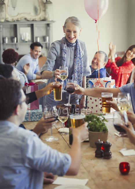 Amigos brindando com taças de vinho e cerveja na festa de aniversário do restaurante — Fotografia de Stock