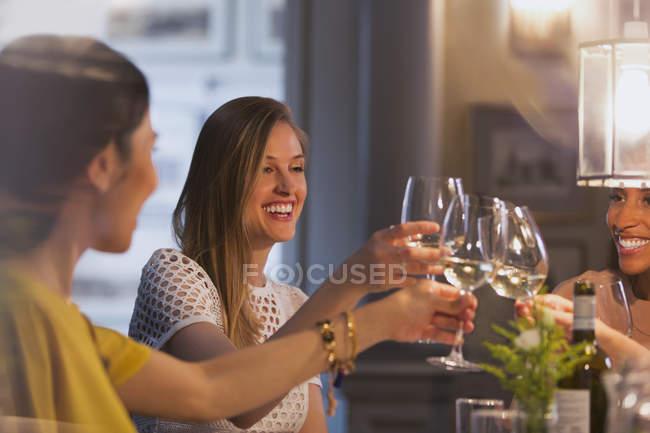 Mulheres sorridentes amigos brindar copos de vinho branco jantar no restaurante — Fotografia de Stock
