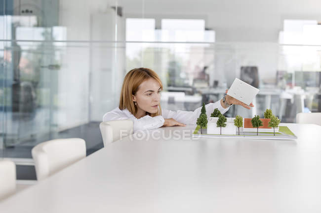 Female architect arranging model in conference room — Stock Photo