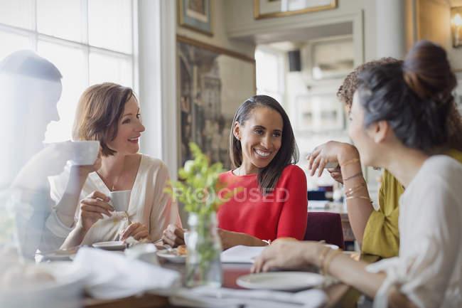 Улыбающиеся подруги обедают, пьют кофе за столом ресторана — стоковое фото