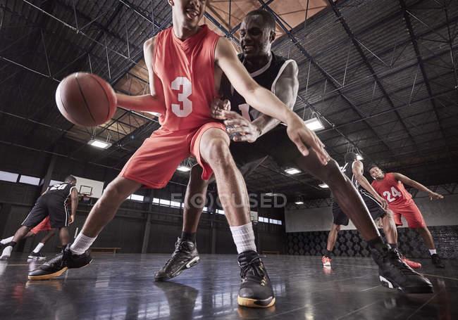 Молодые баскетболисты играют на корте в гимназии — стоковое фото