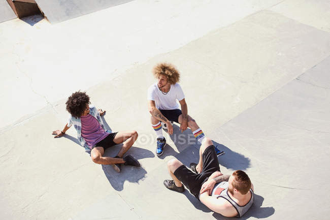 Overhead view male friends hanging out at sunny skate park — Stock Photo