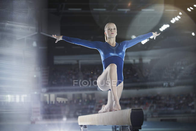 Female gymnast performing on balance beam in arena — Stock Photo