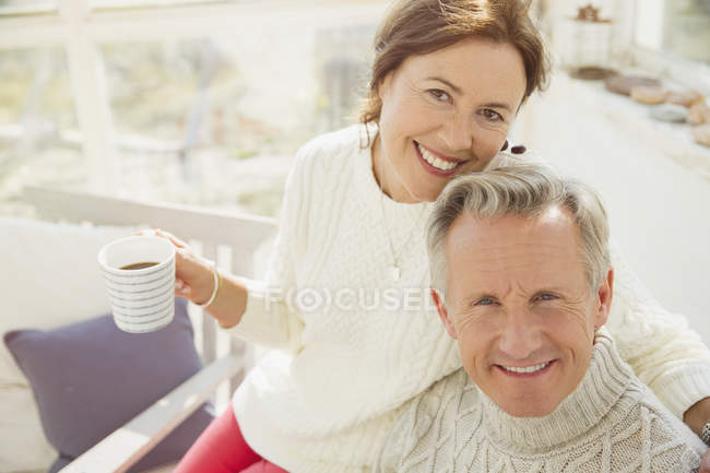 Portrait smiling mature couple hugging and drinking coffee — Stock Photo