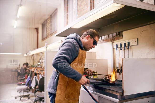 Bijoutier utilisant torche métal chauffant dans l'atelier — Photo de stock
