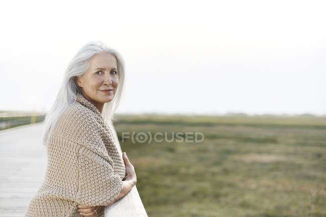 Retrato confiado mujer mayor apoyada en barandilla de paseo marítimo - foto de stock