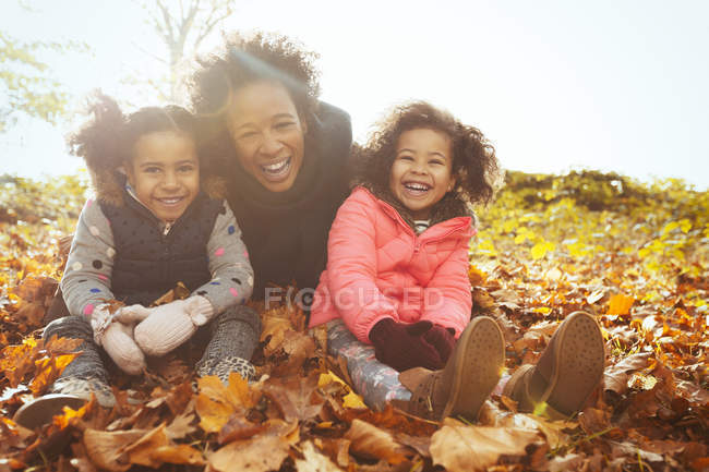 Portrait playful mother and daughters in autumn leaves in sunny park — Stock Photo