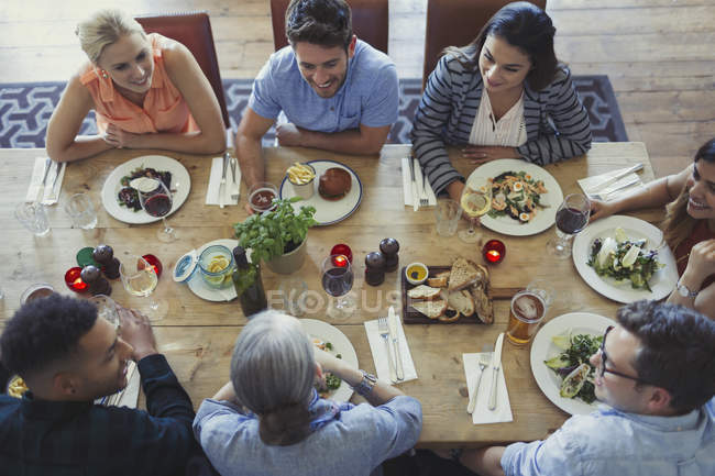 Overhead view friends talking and dining at restaurant table — Stock Photo