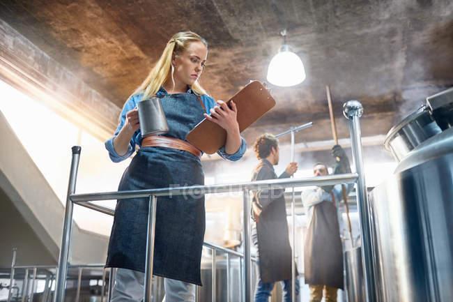 Grille-café femelle regardant vers le bas au presse-papiers près du réservoir — Photo de stock