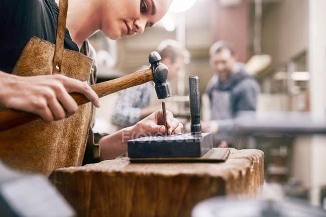 Jeweler using hammer in workshop — Stock Photo