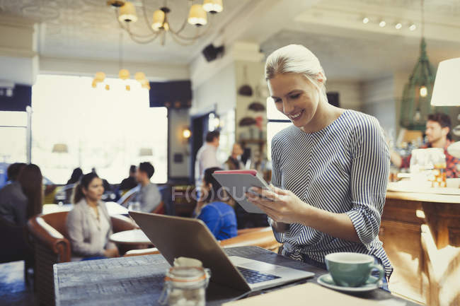 Smiling creative businesswoman using digital tablet and laptop in cafe — Stock Photo