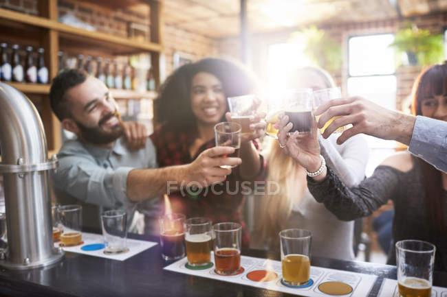 Amigos degustação de cerveja, brindar copos de cerveja no pub — Fotografia de Stock