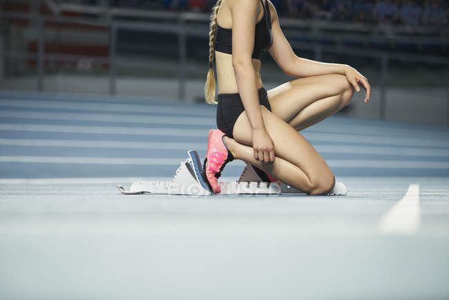 Cropped image of focused female runner ready at starting block on sports track — Stock Photo