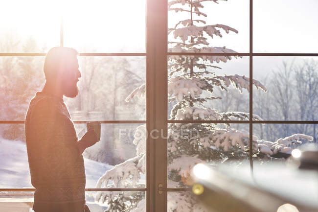 Man drinking coffee at sunny window with view of snowy trees — Stock Photo