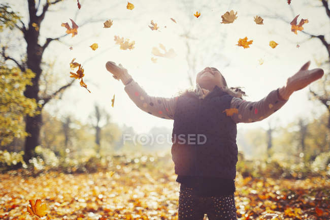 Playful girl throwing autumn leaves overhead in sunny park — Stock Photo