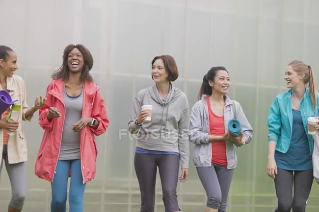 Femmes souriantes marchant avec tapis de yoga et café — Photo de stock