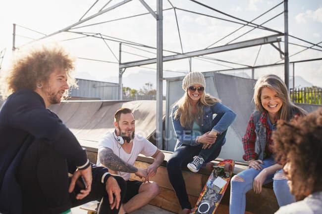 Друзьями болтаться и говорить на Солнечный скейт-парк — стоковое фото