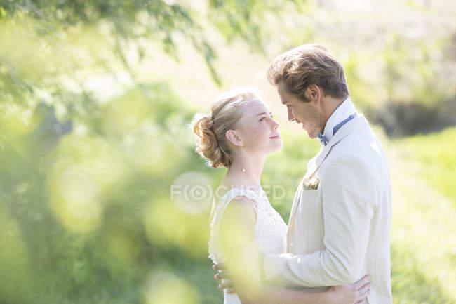 Retrato de jovem casal abraçando no jardim doméstico — Fotografia de Stock