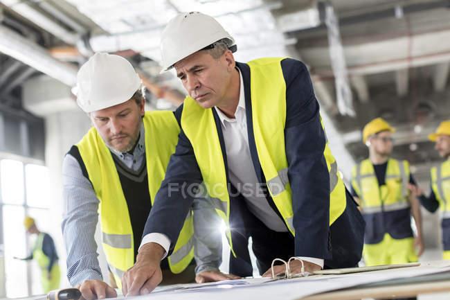 Engenheiros do sexo masculino a ver plantas no local de construção — Fotografia de Stock