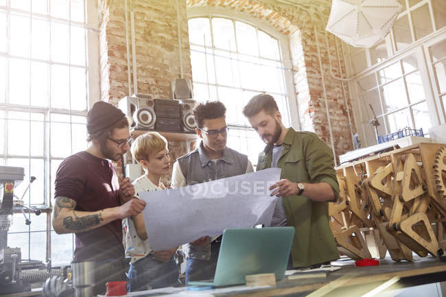 Young designers examining blueprints in workshop — Stock Photo