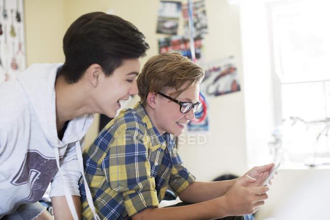 Deux adolescents s'amuser tout en utilisant la tablette numérique dans la salle — Photo de stock