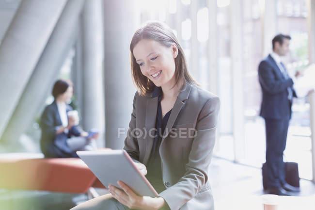 Femme d'affaires souriante utilisant une tablette numérique dans le hall de bureau ensoleillé — Photo de stock