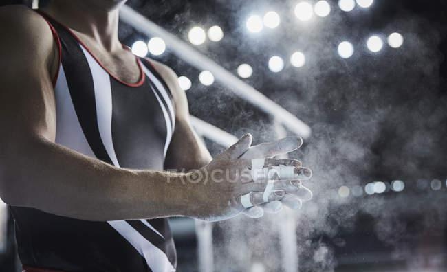 Мужчина гимнаст трения мелом порошок на руках ниже параллельных прутьев — стоковое фото