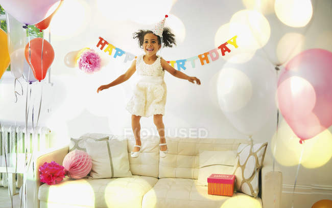 Playful girl jumping on sofa at home — Stock Photo