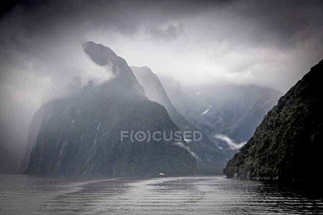 Wolken und Nebel umgeben Klippen, Milford Sound, Südinsel Neuseeland — Stockfoto