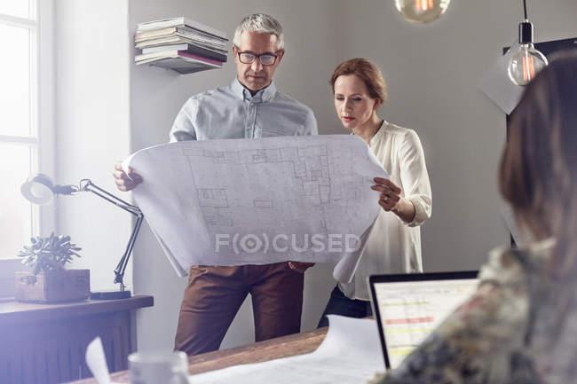 Architectes examinant les plans dans le bureau — Photo de stock