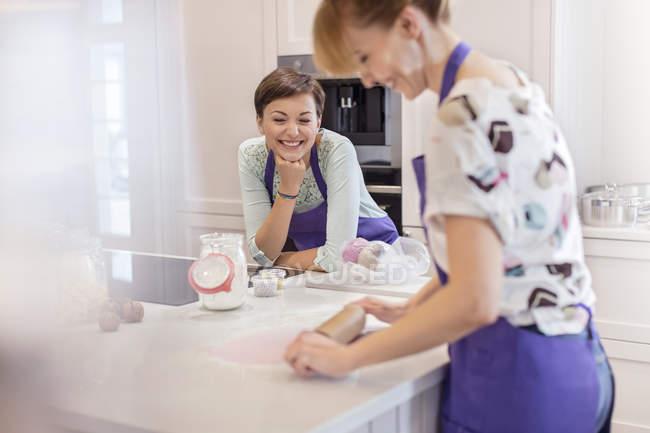 Cuisinières, utilisant le rouleau à pâtisserie dans la cuisine — Photo de stock