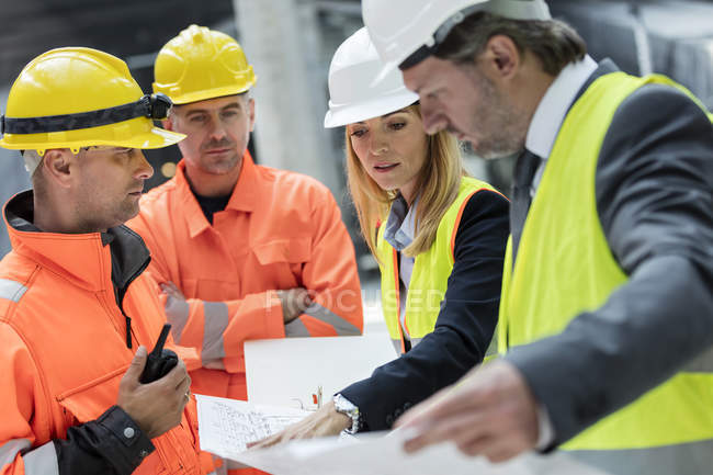 Engineers and construction workers reviewing blueprints at construction site — Stock Photo