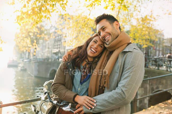 Riendo pareja joven abrazándose en el puente de otoño sobre el canal en Amsterdam - foto de stock