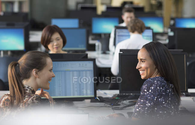 Smiling businesswomen talking at computers in open plan office — Stock Photo