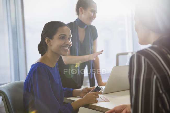Smiling businesswomen talking in conference room meeting — Stock Photo