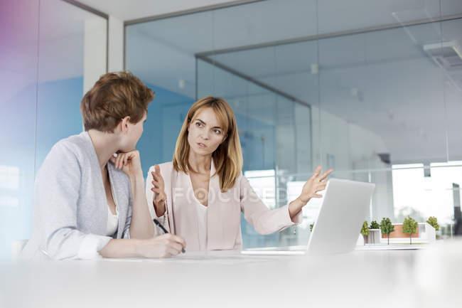 Женщины-архитекторы разговаривают за ноутбуком в конференц-зале — стоковое фото