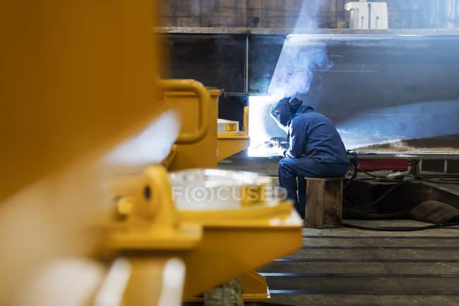 Сварщик с помощью сварочной горелки на сталелитейном заводе — стоковое фото