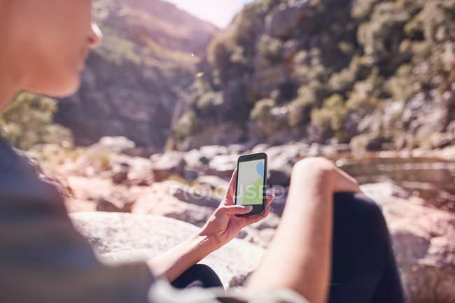 Joven viendo el mapa digital en el teléfono inteligente en el flujo luminoso - foto de stock
