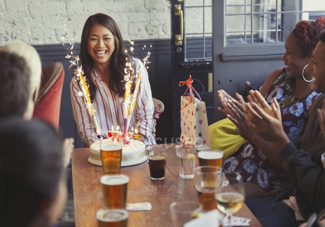Amigos aplaudiendo por mujer feliz con fuegos artificiales pastel de cumpleaños en la mesa del restaurante - foto de stock