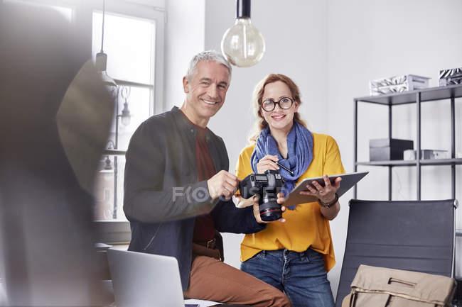 Улыбающиеся портреты, уверенные фотографы с цифровой камерой и цифровым планшетом в офисе — стоковое фото