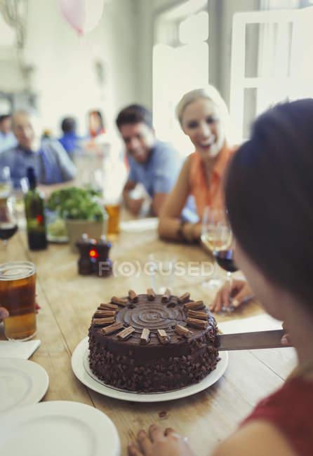 Mujer cortando pastel de cumpleaños de chocolate con amigos en la mesa del restaurante - foto de stock