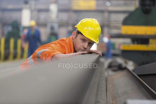 Steel worker examining steel in factory — Stock Photo
