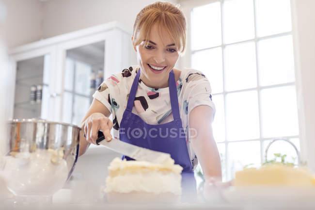 Sourire femme cuisson, glaçage gâteau couche dans la cuisine — Photo de stock
