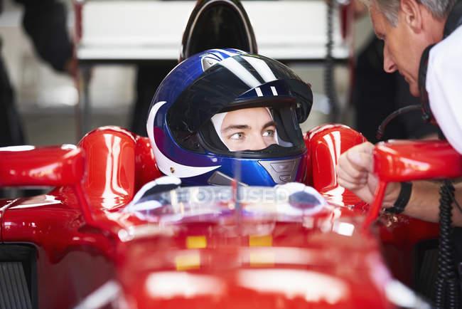 Менеджер говорит с гонщиком Формулы-1 — стоковое фото