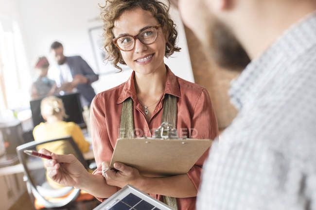 Design professionals with clipboard talking in office — Stock Photo