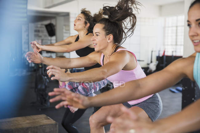 Energetic young women riding elliptical bikes in exercise class — Stock Photo