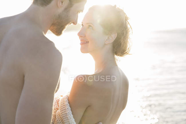 Portrait of smiling young couple in sunlight — Stock Photo